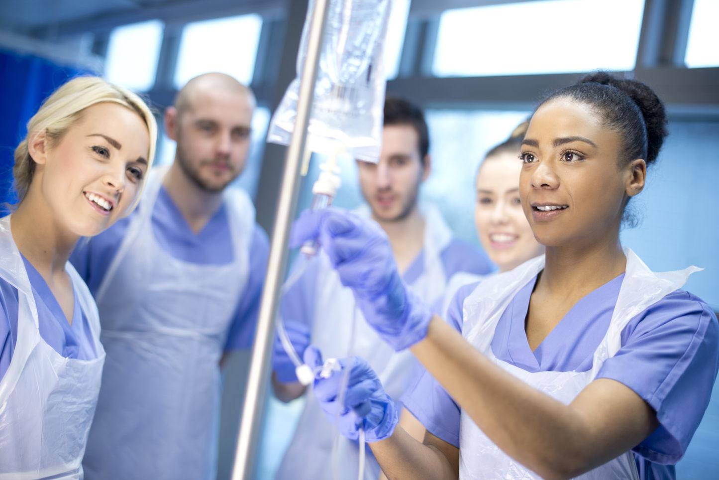 Team of nurses training on handling medical IV equipment